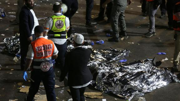 TOPSHOT - Paramedics and ultra-Orthodox Jewish men stand next to covered bodies after dozens of people were killed and others injured after a grandstand collapsed in Meron, Israel, where tens of thousands of people were gathered to celebrate the festival of Lag Ba'omer at the site in northern Israel early on April 30, 2021. - Dozens of people were killed in a stampede at a Jewish pilgrimage site in the north of Israel on early on April 30, rescue services said.  Tens of thousands of Jews were participating in the annual pilgrimage on Thursday, for the feast of Lag BaOmer. But after midnight, a grandstand collapsed, triggering scenes of panic. - Israel OUT (Photo by David COHEN / JINI PIX / AFP) / Israel OUT (Photo by DAVID COHEN/JINI PIX/AFP via Getty Images)