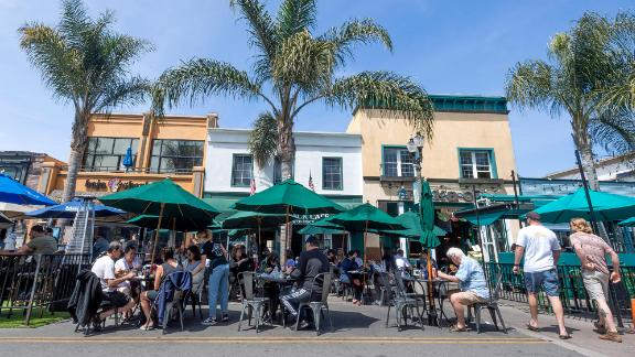 """People eat outside along Main St. in Huntington Beach, CA on Tuesday, April 6, 2021. """"nState health officials announced schools and businesses in California should be able to fully reopen at their pre-pandemic capacities starting June 15. (Photo by Paul Bersebach/Orange County Register via Getty Images)"""