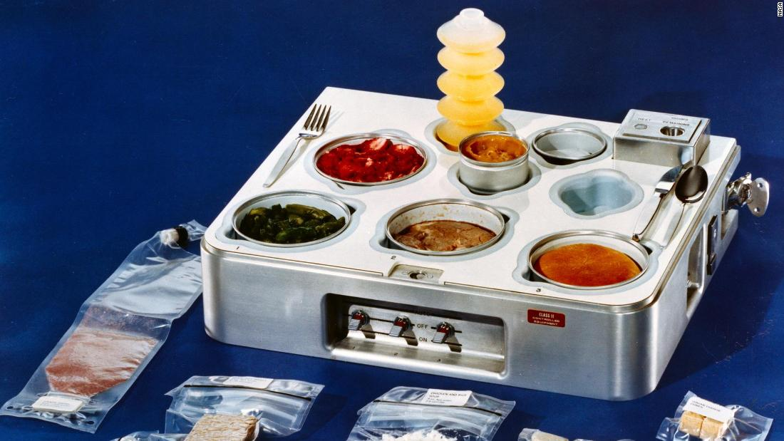 This food tray was used in the now-defunct Skylab, the first US space station launched by NASA in 1973. Shown in the tray are (counterclockwise from back): orange drink, strawberries, asparagus, prime rib, dinner roll and  butterscotch pudding.