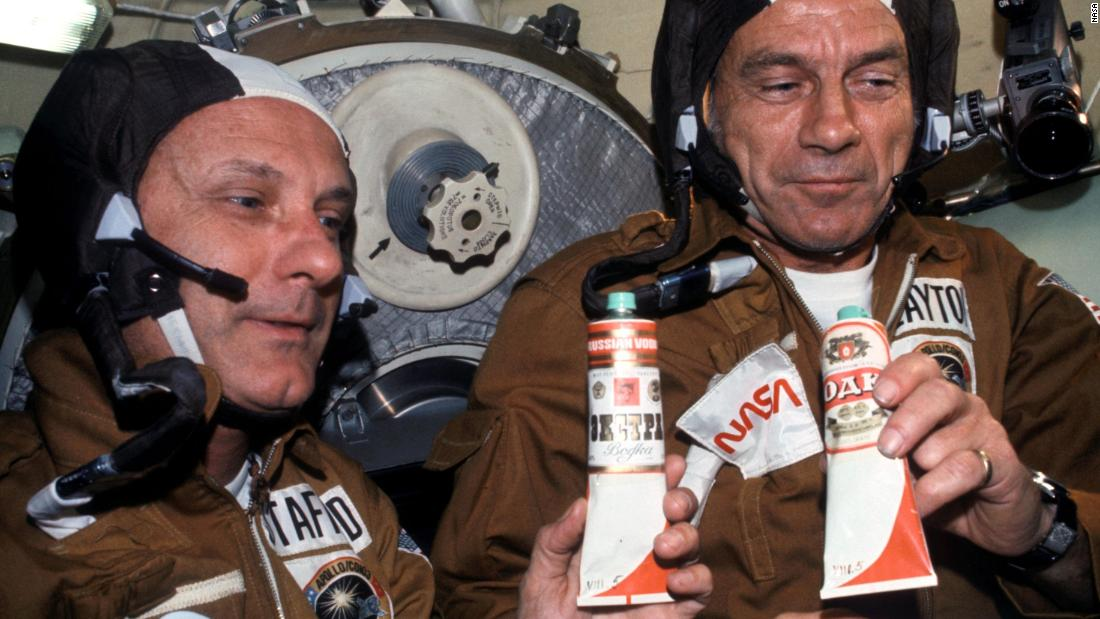 "NASA Astronauts Thomas P. Stafford (left) and Donald K. ""Deke"" Slayton (right) hold containers of Soviet space food in the Soyuz Orbital Module during a nine-day joint US-USSR space mission in July 1975. The containers -- over which vodka labels have been pasted -- hold borscht (beet soup). This was the crews' way of toasting each other."