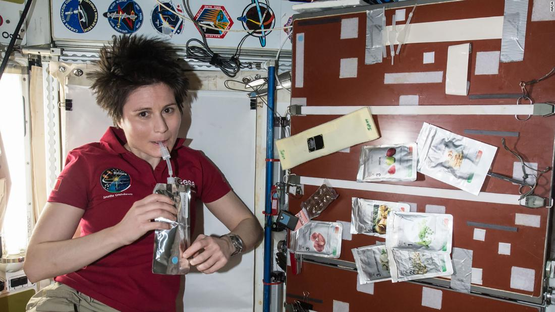 European Space Agency astronaut Samantha Cristoforetti is seen taking a drink in the Unity module aboard the International Space Station, April 27, 2015. The crew's food galley is located in Unity; several food packets are visible to the right.