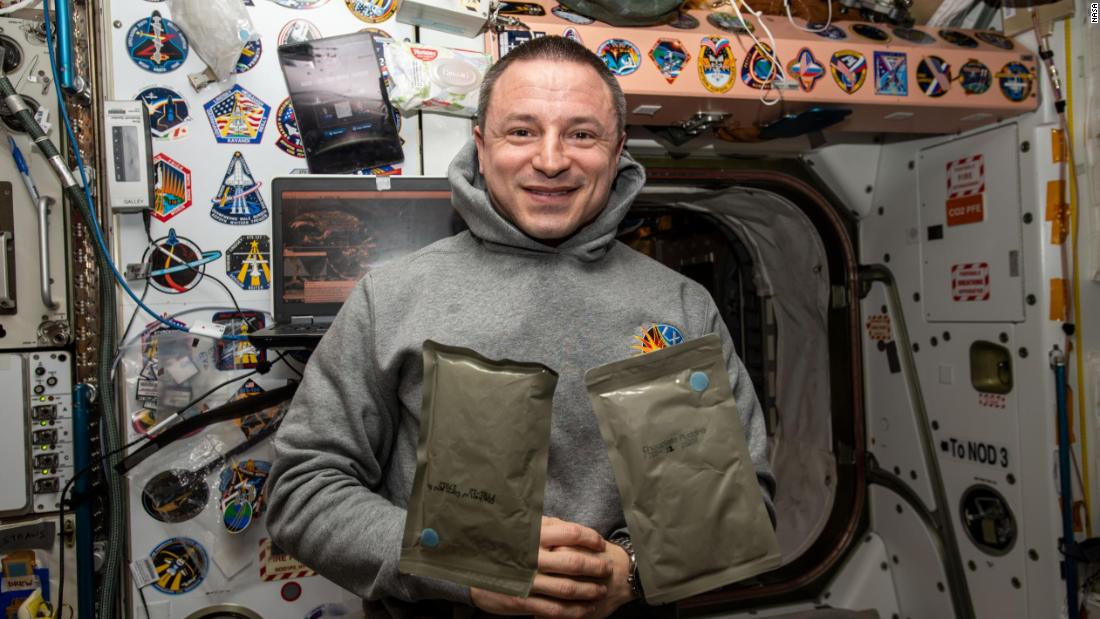 NASA astronaut and Expedition 61 Flight Engineer Andrew Morgan poses with two food packets, chicken with cornbread and chocolate pudding, during dinnertime aboard the International Space Station's Unity module, January 1, 2019.