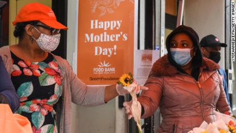 NEW YORK, NY - MAY 08: Food pantry workers arrange flowers to be given to clients at The Community Kitchen and Food Pantry on May 8, 2020 in the Harlem neighborhood in New York City. The Food Bank of New York City in conjunction with this food pantry is distributing baby products, food and flowers in honor of Mother's Day. (Photo by Stephanie Keith/Getty Images)