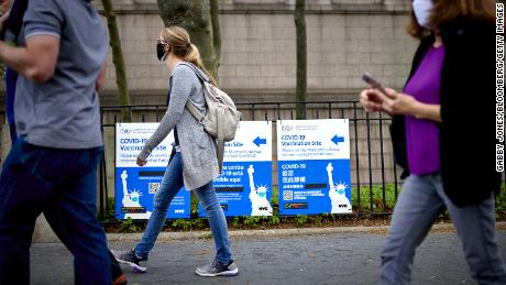 Pedestrians pass in front of a COVID-19 vaccination site sign outside the American Museum of Natural History in New York on April 30, 2021.