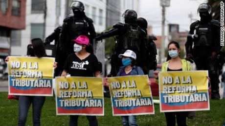 Les femmes tiennent des banderoles indiquant «Non à la réforme fiscale». comme la police monte la garde.
