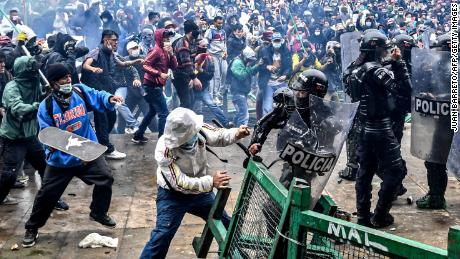 TOPSHOT - Demonstrators clash with riot police during a protest against a tax reform bill launched by Colombian President Ivan Duque, in Bogota, on April 28, 2021. - Workers' unions, teachers, civil organizations, indigenous people and other sectors reject the project that is underway in the Congress, considering that it punishes the middle class and is inappropriate in the midst of the crisis unleashed by the COVID-19 pandemic. (Photo by Juan BARRETO / AFP) (Photo by JUAN BARRETO/AFP via Getty Images)