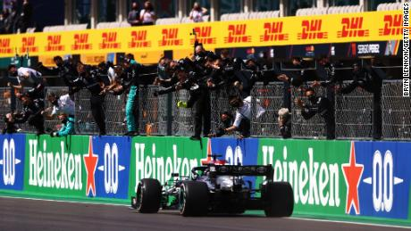 Mercedes team members celebrate on the pitwall as Lewis Hamilton crosses the finish line to win the Portuguese Grand Prix.