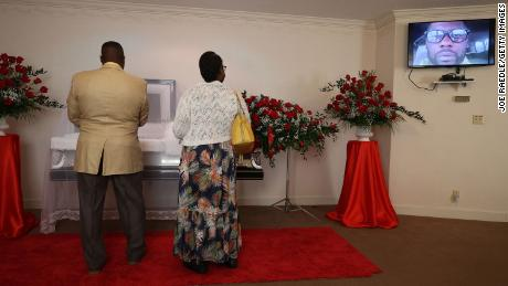A photograph of Andrew Brown Jr.  appears on a screen while Edwin Newby and Ella Newby respect him during a viewing at Horton's Funeral Home and Cremations Chapel on May 2, 2021 in Hertford, North Carolina.