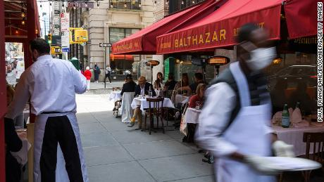 Guests dine on an outdoor patio in New York City on April 27, 2021