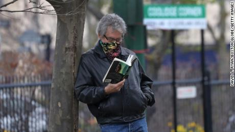 A man wears a mask while reading outdoors in Brookline, Massachussetts, in April 2020.