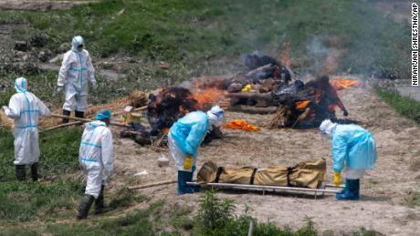 Des hommes népalais en tenue de protection individuelle brûlent les corps des victimes du COVID-19 près du temple de Pashupatinath à Katmandou, au Népal, le 3 mai 2021.