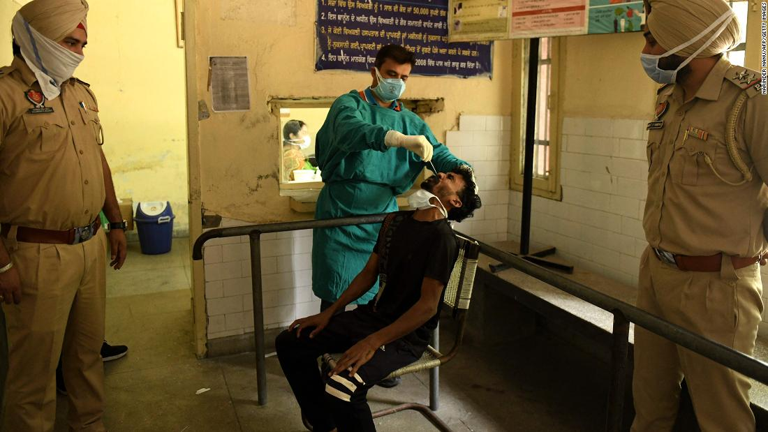 A health worker administers a Covid-19 test on the outskirts of Amritsar, India, on Monday, May 3. Police in rural areas launched a free cab service for villagers so they could get tested and vaccinated.