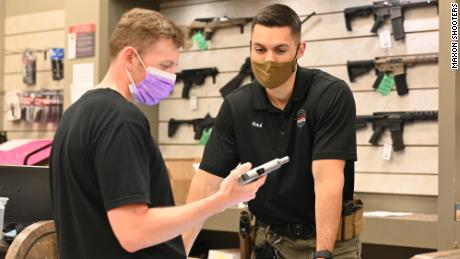 A prospective customer inspects a handgun at Maxon Shooter's Supplies & Indoor Range in Des Plaines, Illinois.