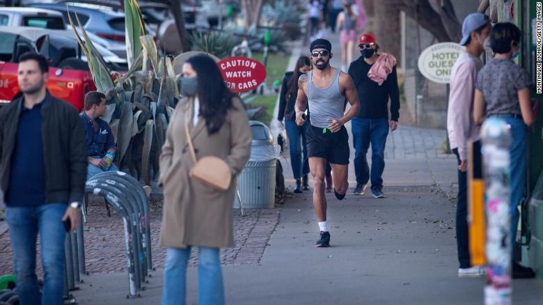 Pedestrians walk  in Austin before Texas Gov. Greg Abbott ended the state's mask mandate in March.