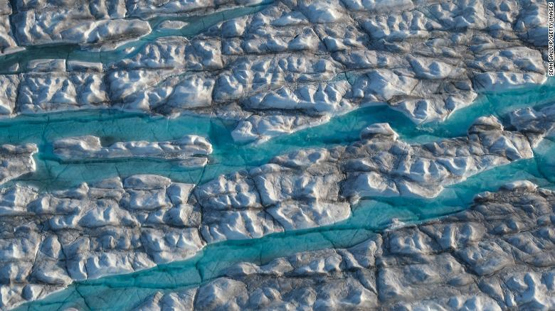 Rivers of meltwater carve into the Greenland ice sheet. A new study finds that limiting warming to below 1.5 degrees Celsius could cut sea level rise caused by melting land ice this century in half.