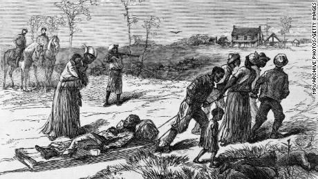 Black Americans gather dead and wounded following the Colfax Massacre in Louisiana.
