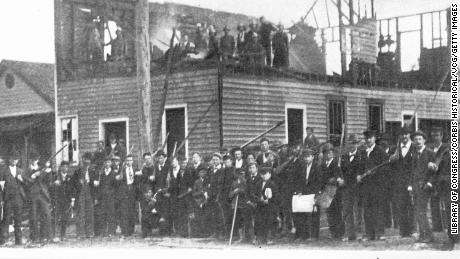 White supremacists gather outside the scorched remains of Wilmington's Daily Record newspaper building following the 1898 massacre.