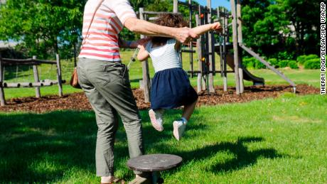 Illustration picture shows an adult holding a girl playing in a playground in Brussels, Wednesday 27 May 2020. From Today, municipalities can re-open the play areas for children under twelf. Belgium is in its eleventh week of confinement in the ongoing corona virus crisis and the second week of the phase 2 of the deconfinement. The National Security Council has given the Go to the deconfinement in stages as developed by the Group of Experts for the Exit Strategy. BELGA PHOTO THIERRY ROGE (Photo by THIERRY ROGE/Belga/Sipa USA)(Sipa via AP Images)