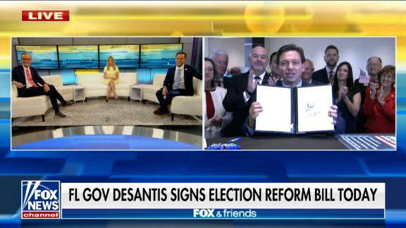 Florida Gov. Ron Desantis holds up the voting bill after signing it on Fox News live. The cable news network was the only press outlet granted access to the signing.