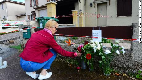 A woman lays flowers outside the house where a 31-year-old French mother of three was burned alive by her husband, on May 5, 2021 in Merignac. - The man chased her down the street and shot her in the legs before dousing her in a flammable liquid and setting her alight. He was arrested half an hour after the murder in the neighbouring district of Pessac, armed with a pistol, a pellet gun and a cartridge belt, the Bordeaux prosecutor's office said. (Photo by MEHDI FEDOUACH / AFP) (Photo by MEHDI FEDOUACH/AFP via Getty Images)