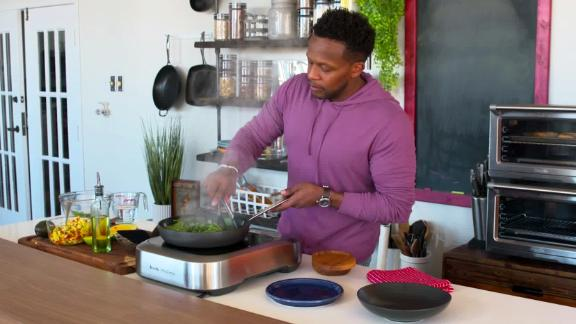 Curry prepares salmon with spinach, cauliflower rice, and mango salsa in his Dallas test kitchen.