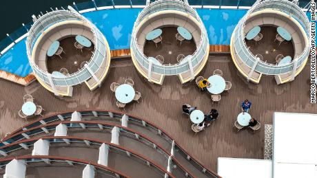 Passengers sit on the deck on board of the Costa Smeralda cruise ship in Savona, near Genoa on May 1, 2021. - Italian cruise line Costa Cruises set sail on May 1, 2021, for the first time in more than four months, buoying an industry capsized by the Covid-19 pandemic. (Photo by Marco Bertorello / AFP) (Photo by MARCO BERTORELLO/AFP via Getty Images)