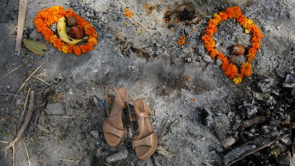 Flower garlands, fruits and a pair of sandals were placed on a spot where a woman was cremated in New Delhi on April 30.
