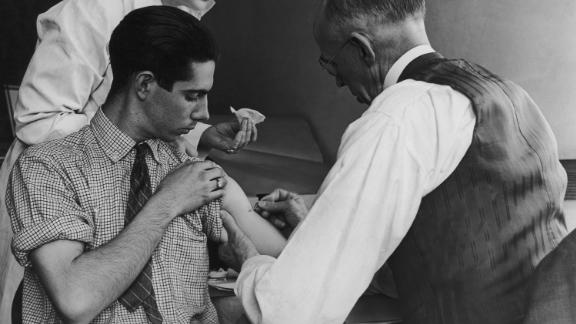 A school doctor and nurse deliver a smallpox vaccination in 1938 to a teen in Gasport, New York.