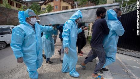 Familieleden dragen het lichaam van een Covid-19-slachtoffer tijdens een begrafenisstoet in Srinagar op 7 mei.