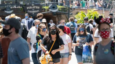 Guests wearing protective masks walk past the Pirates of the Caribbean attraction during the reopening of the Disneyland.