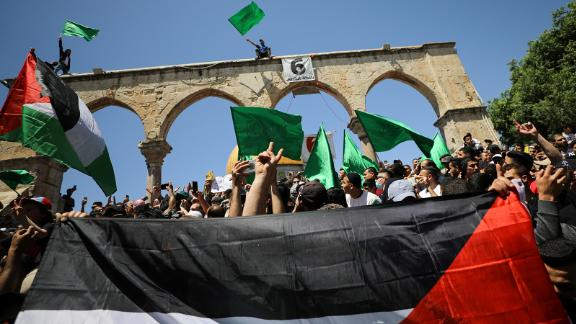 People hold flags as Palestinians gather after performing the last Friday of Ramadan to protest over the possible eviction of several Palestinian families from homes on land claimed by Jewish settlers in the Sheikh Jarrah neighbourhood, in Jerusalem's Old City, May 7, 2021. REUTERS/Ammar Awad