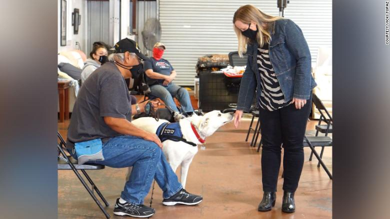 Author Shauna Springer gently extends the back of her hand as she visits with a service dog at Operation Freedom Paws.