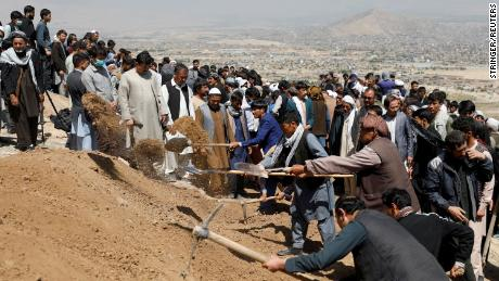 Des hommes creusent des tombes pour les victimes de l'explosion de samedi lors d'une cérémonie funéraire de masse à Kaboul.