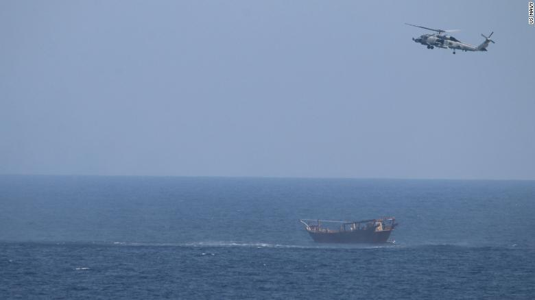An SH-60 Sea Hawk helicopter assigned to the guided-missile cruiser USS Monterey flies above a stateless dhow interdicted with a shipment of illicit weapons in international waters of the North Arabian Sea on May 6, 2021.