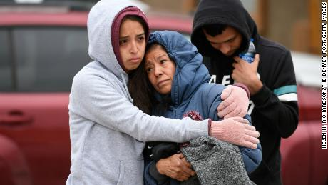 Family members of some of the shooting victims hug one another outside the scene of the shooting at the Canterbury Mobile Home Park on May 9, 2021, in Colorado Springs, Colorado.