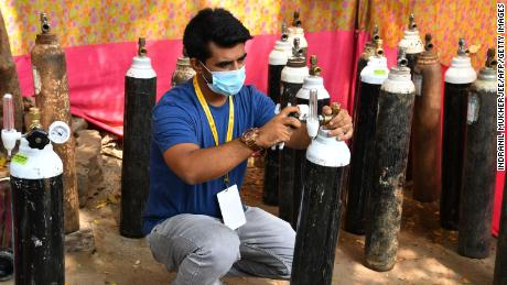 Shahnawaz Shaikh checks the pressure of an oxygen cylinder at a distribution center in Mumbai on April 28, 2021.