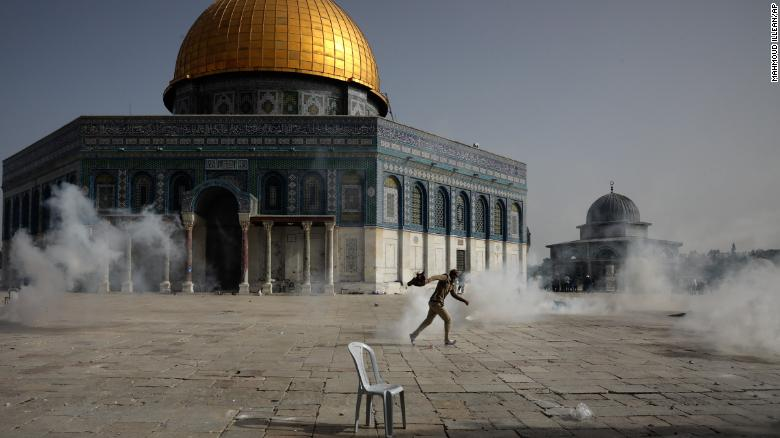 A Palestinian man runs from tear gas during clashes with Israeli security forces in front of the Dome of the Rock on Monday.