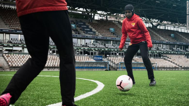 A player dribbles with a ball while wearing a Nike Pro hijab.