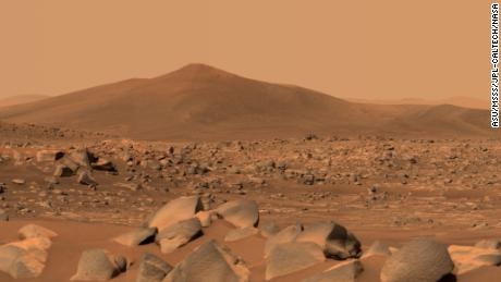 "NASA's Perseverance Mars rover used its dual-camera Mastcam-Z imager to capture this image of ""Santa Cruz,"" a hill about 1.5 miles (2.5 kilometers) away from the rover, on April 29, 2021, the 68th Martian day, or sol, of the mission. The entire scene is inside of Mars' Jezero Crater; the crater's rim can be seen on the horizon line beyond the hill. This scene is not white balanced; instead, it is displayed in a preliminary calibrated version of a natural-color composite, approximately simulating the colors of the scene as it would appear to a person on Mars. An enhanced color version is also included."