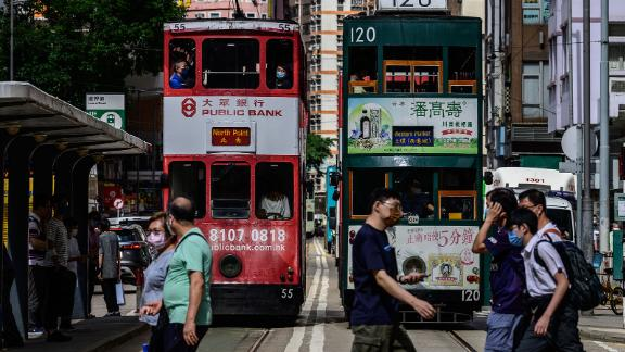 Pedestrians walk across a road in front of commuter trams in Hong Kong on May 11, 2021. (Photo by Anthony WALLACE / AFP) (Photo by ANTHONY WALLACE/AFP via Getty Images)