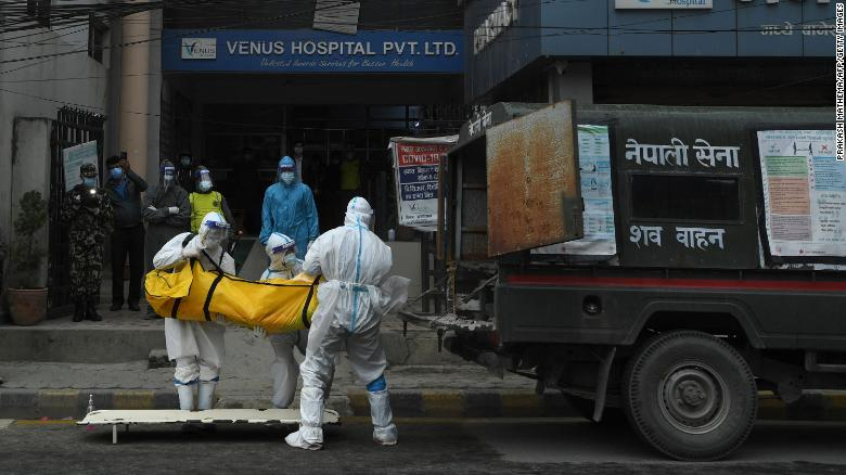 Nepal army personnel wearing personal protective equipment (PPE) load the body of a person who died from Covid-19 coronavirus before taking it to a crematorium in Kathmandu on May 5, 2021.