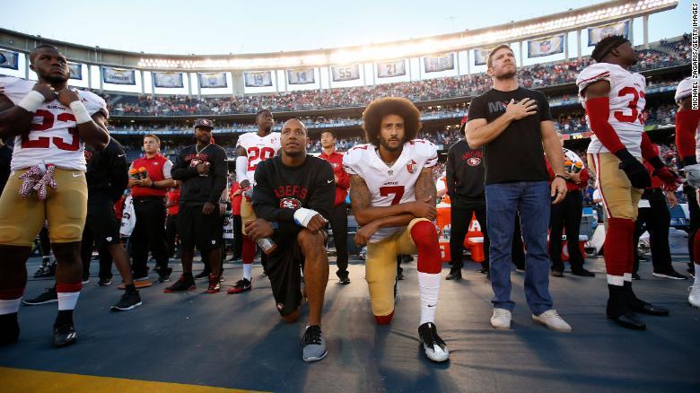 Eric Reid dan Kaepernick berlutut di pinggir lapangan saat menyanyikan lagu kebangsaan