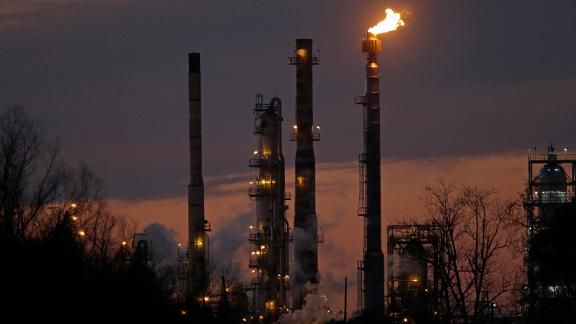 FILE - In this Feb. 13, 2015 file photo, stacks and burn-off from the ExxonMobil refinery are seen at dusk in St. Bernard Parish, La. New York City officials say they will begin the process of dumping about $5 billion in pension fund investments in fossil fuel companies, including Exxon Mobil, because of environmental concerns. (AP Photo/Gerald Herbert, File)