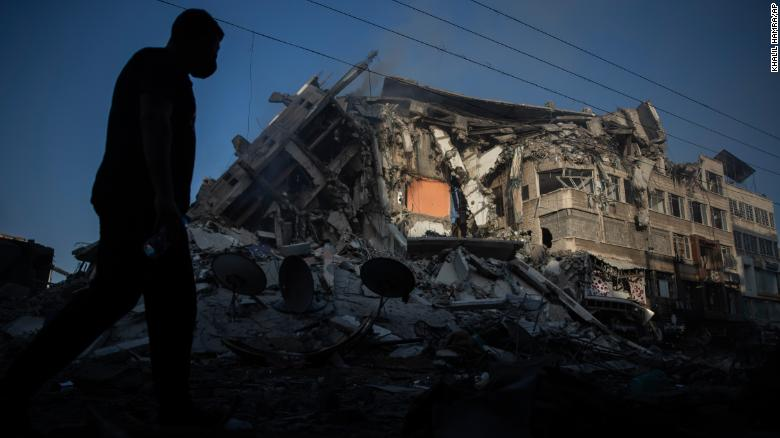 A Palestinian walks next to a building destroyed by Israeli airstrikes in Gaza City on Thursday, May 13.