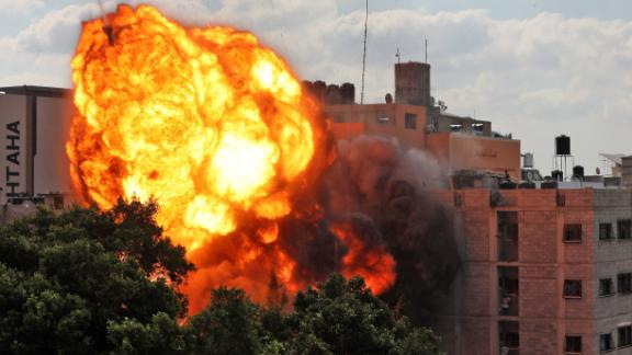 A fireball engulfs the Al-Walid building which was destroyed in an Israeli airstrike in Gaza City, early on May 13.