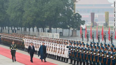 Afghanistan's President Hamid Karzai walks with China's President Xi Jinping as they review an honour guard during a welcoming ceremony at the Great Hall of the People in Beijing on September 27, 2013.