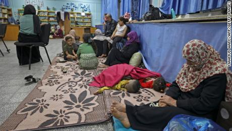 Palestinian families take shelter in a UN school in Gaza City on May 13, 2021, after fleeing from their homes in the town of Beit Lahia.