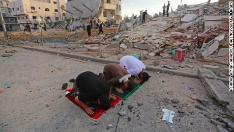 Palestinians perform Eid al-Fitr prayers near buildings destroyed by ongoing Israeli airstrikes in Beit Lahia, Gaza, on May 13.