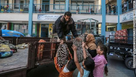Palestinians unload their belongings at a UN school in Gaza City where they are taking shelter after fleeing their homes in the Shejaiya neighborhood.