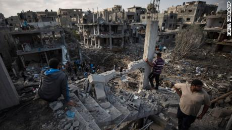 Palestinians inspect destroyed buildings following overnight Israeli airstrikes in the town of Beit Hanoun, Gaza, on Friday, May 14.